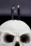 Couple of businessmen in miniature handshaking over a skull Royalty Free Stock Photography