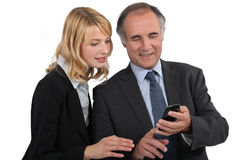 A couple of businesspeople. Looking at a cell phone royalty free stock images