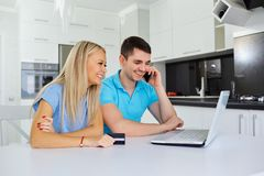 A couple buyers with a credit card make purchases at home with a stock photo