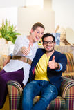 Couple buying armchair in furniture store Royalty Free Stock Photos