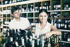 Couple buying bottle of wine Royalty Free Stock Images