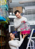 Couple buying cage for bird in shop Royalty Free Stock Photos