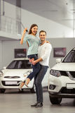 Couple buying a car. Beautiful young couple is smiling, looking at camera and showing keys while buying a car in a motor show. Man is holding women in his arms Stock Image