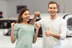 Couple buying a car. Beautiful young couple is smiling, showing keys and Ok sign while buying a car in a motor show royalty free stock image