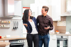 Couple buying domestic kitchen furniture store. Man and women buying domestic kitchen in studio or furniture store Royalty Free Stock Photos
