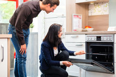 Couple buying domestic kitchen in showroom Stock Photo