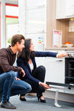 Couple buying domestic kitchen in showroom Stock Photos