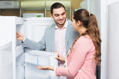 Couple buying domestic refrigerator Royalty Free Stock Images