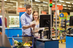 Couple buying food at grocery at cash register Royalty Free Stock Images