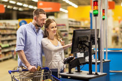 Couple buying food at grocery at cash register Royalty Free Stock Photo