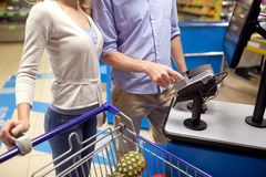 Couple buying food at grocery self-checkout. Shopping, sale, payment, consumerism and people concept - couple with bank card buying food at grocery store or Stock Images