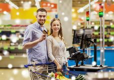 Couple buying food at grocery self-checkout. Shopping, sale, payment, consumerism and people concept - happy couple with bank card buying food at grocery store Royalty Free Stock Images
