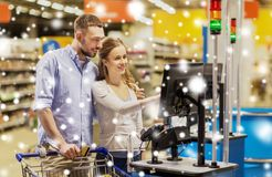 Couple buying food at grocery self-checkout. Shopping, sale, payment, consumerism and people concept - happy couple with bank card buying food at grocery store Stock Image