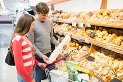 Couple buying French baguette Stock Images