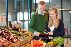 Couple Buying Groceries with List on Phone Stock Photography