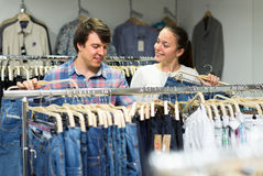 Couple buying jeans in shopping center Stock Images