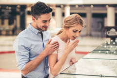 Couple buying jewelry. Beautiful couple is smiling while choosing jewelry in the shopping mall stock photos