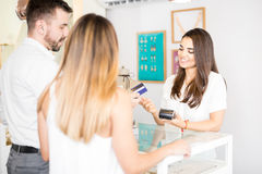 Couple buying jewelry with a credit card. Good looking young women working at a jewelry store and receiving a payment from a couple with a credit card royalty free stock images