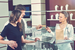 Couple buying jewelry in store and paying with card. Royalty Free Stock Photo