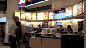 Couple buying juice at food court inside Coquitlam center mall stock footage