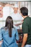 Couple Buying Meat From Butcher Shop Royalty Free Stock Image