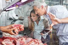 Couple Buying Meat At Butchery Royalty Free Stock Image