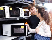 Couple buying microwave oven in hypermarket and smiling Royalty Free Stock Photos