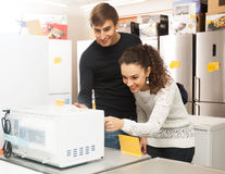 Couple buying microwave oven Royalty Free Stock Photo