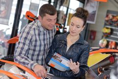 Couple buying motorbike in workshop Royalty Free Stock Images