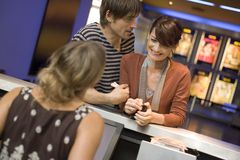 A couple buying movie tickets at the box office. Royalty Free Stock Images