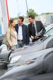 Couple buying new car with car salesman Stock Image