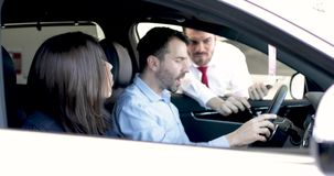 Couple buying a new car in dealership stock footage