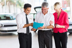 Couple buying new car. Mature couple buying a new car at vehicle showroom Royalty Free Stock Photos