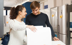Couple buying new clothes washer. Happy family couple buying new clothes washer in supermarket royalty free stock image