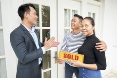 Couple buying the new house. Happy young couple buying the new house standing near the entrance door together with realtor who clapping hands and congratulating royalty free stock photo