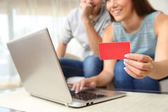 Couple buying online with bank card. Close up of a couple buying on line with bank card and a laptop sitting on a sofa in the living room at home Stock Image