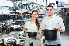 Couple buying pans in shop cookware. Happy young couple choosing new pans for home kitchen in shop cookware royalty free stock photo