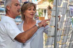 Couple buying postcards. Whilst on holiday Royalty Free Stock Photo