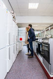 Couple Buying Refrigerator In Hypermarket Royalty Free Stock Photos