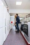 Couple Buying Refrigerator In Hypermarket Royalty Free Stock Photos
