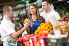 Couple buying from salesman at street market royalty free stock image