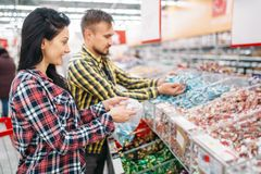 Couple buying sweets and candies in supermarket. Happy couple buying sweets and candies in supermarket. Male and female customers on family shopping. Man and stock photos