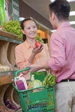 Couple buying vegetables in supermarket, holding basket Stock Image