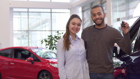 Couple buys car at the dealership. Young interracial couple buying car at the dealership. Handsome african american man embracing his girlfriend against stock footage