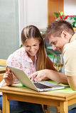 Couple in café looking at laptop Stock Photo