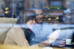 Couple in cafe. Young couple using tablet in coffee shop Stock Image