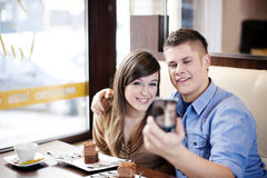 Couple in cafe. Couple taking picture in cafe Royalty Free Stock Photography