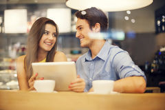 Couple in cafe. Flirting couple in cafe using digital tablet Stock Image