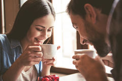 Couple at the cafe. Happy young couple is drinking coffee and smiling while sitting at the cafe Stock Photo