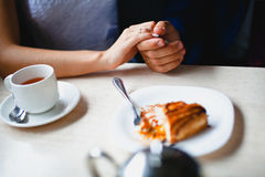 Couple in a cafe held by hand piece of cake Royalty Free Stock Image